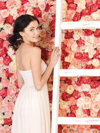 young woman with old ladder and background full of roses photo