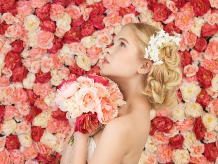 woman with bouquet of flowers and background full of roses photo