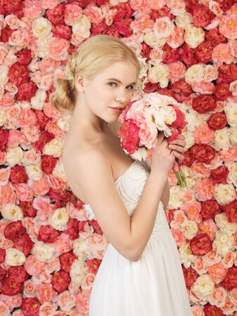 innocent girl: woman with bouquet of flowers and background full of roses Stock Photo