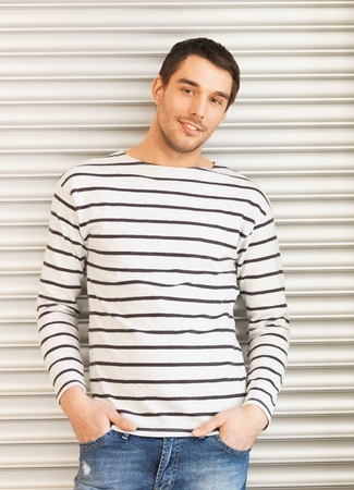 young male model: portrait of handsome man in casual clothes leaning to wall Stock Photo