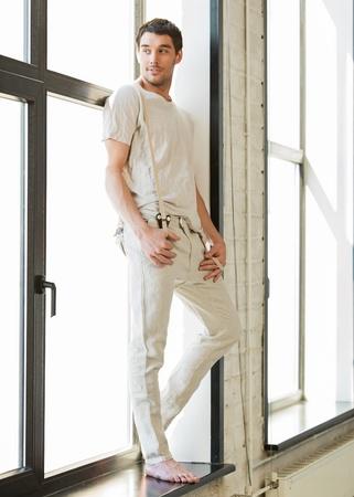 barefoot man: portrait of handsome man standing on the windowsill