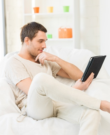 man couch: handsome man sitting on the couch with tablet pc