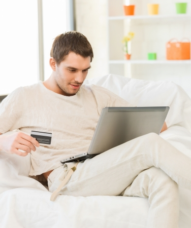 picture of young man with laptop and credit card at home photo