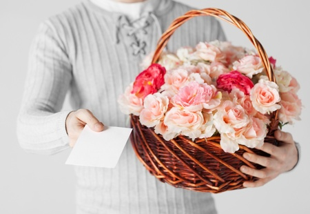 flower basket: close up of man holding basket full of flowers and postcard  Stock Photo