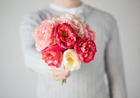 propose: close up of young man giving bouquet of flowers