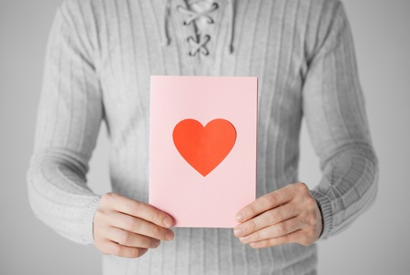 man close up: close up of man holding postcard with heart shape