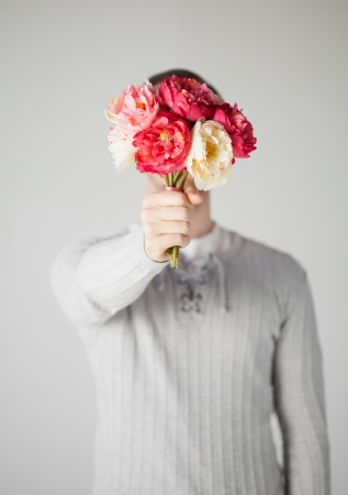 young man covering his face with bouquet of flowers  Stock Photo - 19001286