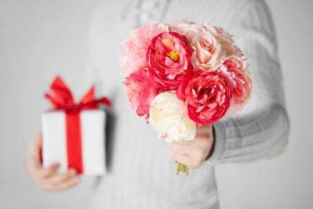 close up of man holding bouquet of flowers and gift box Stock Photo - 19001287