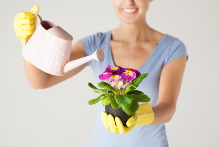 woman holding pot with flower and watering can photo