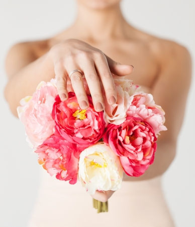 close up of bride with bouquet of flowers and wedding ring  photo