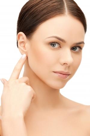 cosmetic surgery: face of beautiful woman touching her ear