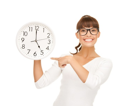 running out of time: attractive businesswoman pointing her finger at wall clock