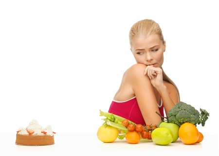 versus: picture of doubting woman with fruits and hamburger Stock Photo