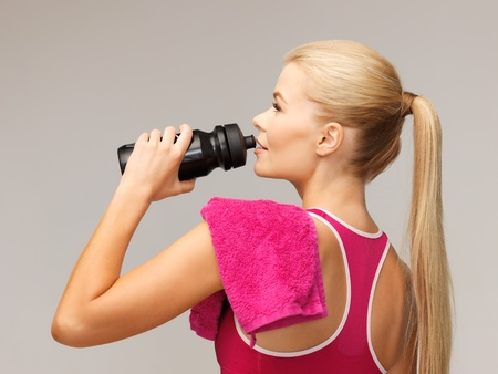 picture of sporty woman drinking water from sportsman bottle photo