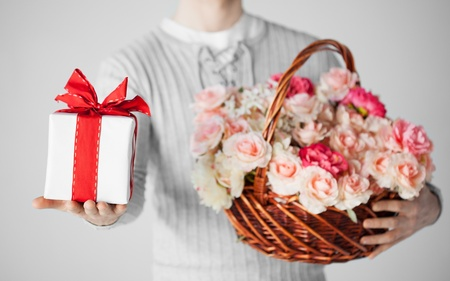 close up of man holding basket full of flowers and gift box  photo