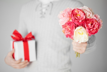 close up of man holding bouquet of flowers and gift box  photo