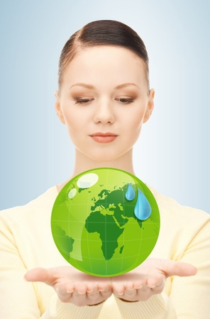 forest conservation: close up of woman holding green globe in her hands
