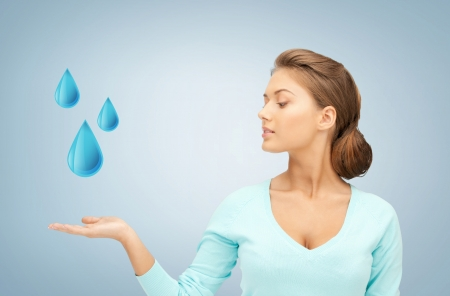 woman showing blue water drops on her hand Stock Photo - 19146334