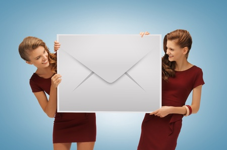 two lovely girls holding big envelope ang looking at each other photo