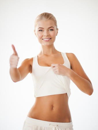 6 pack: beautiful sporty woman showing thumbs up and her abs