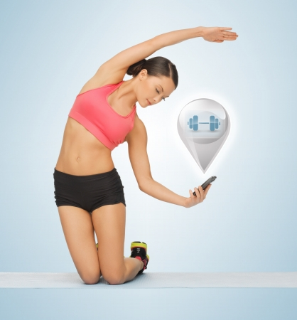 beautiful sporty woman with smartphone doing exercise photo