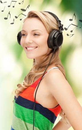 personas escuchando: Foto de mujer feliz y sonriente con los auriculares Foto de archivo