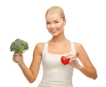 young woman holding heart symbol and broccoli photo