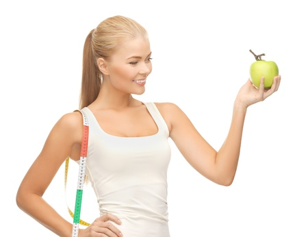 woman measuring: beautiful sporty woman with apple and measuring tape