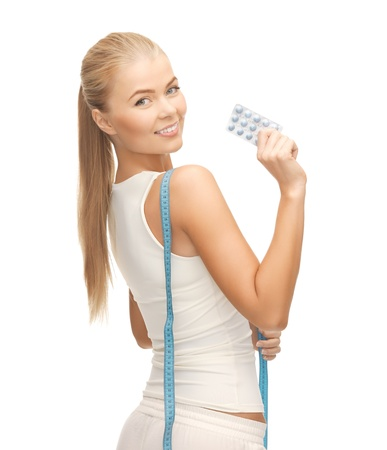 sporty woman with measuring tape and diet pills photo