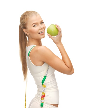 beautiful sporty woman with apple and measuring tape
