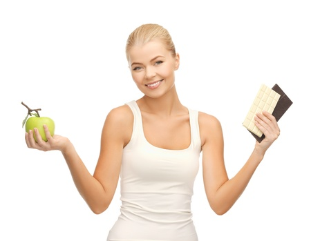 picture of sporty woman with apple and chocolate bars photo