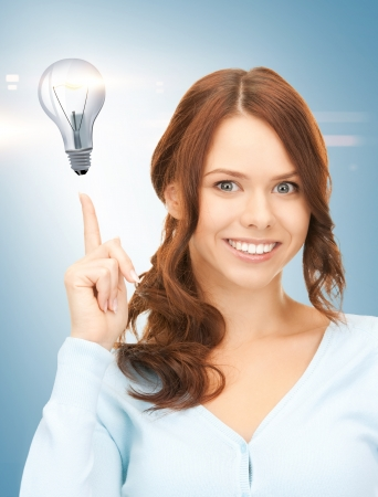 beautiful woman pointing her finger at light bulb Stock Photo - 19207235