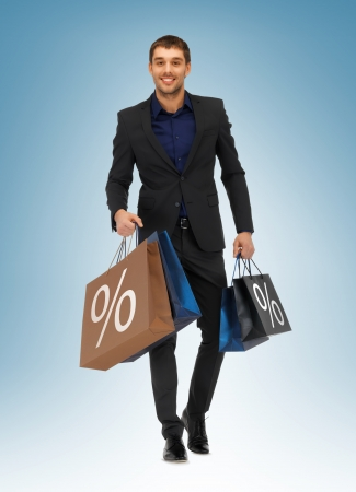consumerism: picture of handsome man with shopping bags