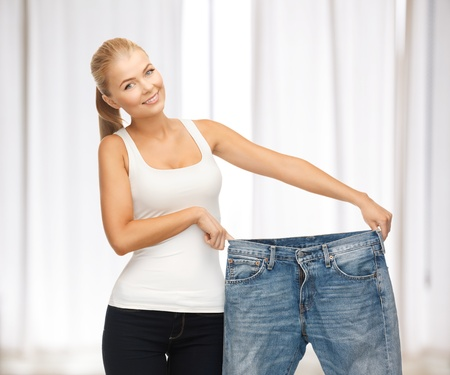 weigh: picture of sporty woman showing big pants Stock Photo