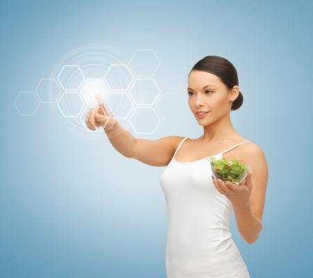 vitamina: mujer con ensalada y trabajar con la pantalla virtual