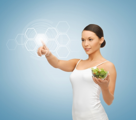woman holding salad and working with virtual screen