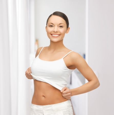 happy woman taking off blank white t-shirt photo