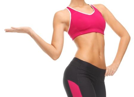 ropa deportiva: cerca de la mujer con abdominales entrenados mostrando algo Foto de archivo