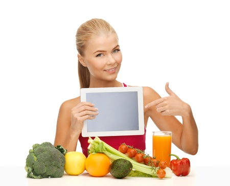 computer program: sporty woman with fruits and vegetables pointing at tablet pc Stock Photo