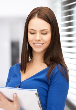picture of smiling young businesswoman taking notes photo