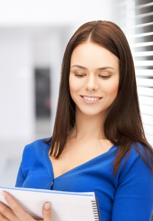 picture of smiling young businesswoman reading notes photo
