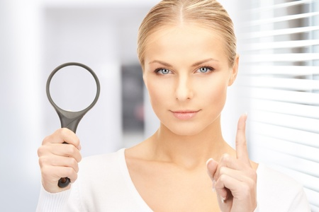 picture of woman with magnifying glass in office photo