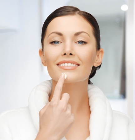 picture of woman in bathrobe applying cream Stock Photo - 19229393
