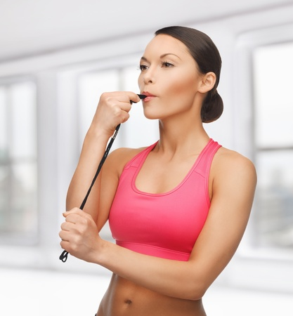 sporty woman with whistle looking at something photo