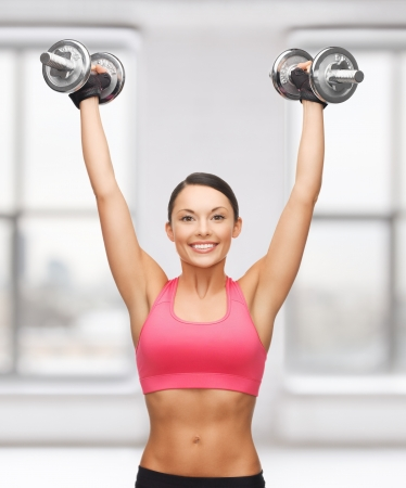 six packs: picture of young sporty woman with heavy steel dumbbells Stock Photo