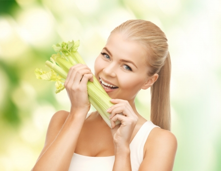 picture of woman biting piece of celery or green salad photo