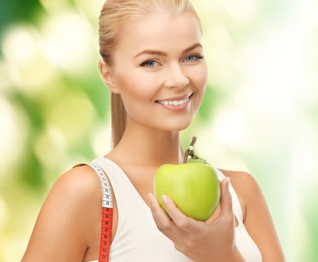 beautiful sporty woman with apple and measuring tape photo