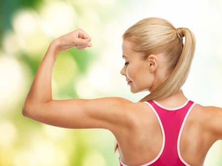 showing muscles: picture of young sporty woman showing her biceps
