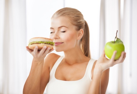 healthy woman smelling hamburger and holding apple photo
