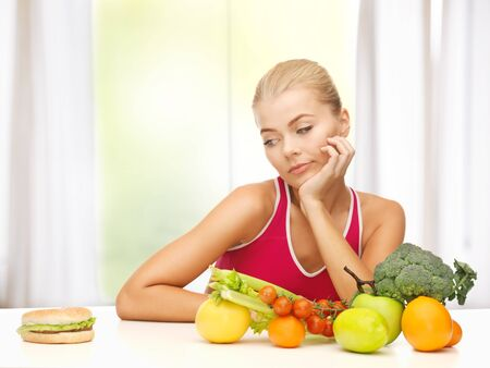 carbohydrates food: picture of doubting woman with fruits and hamburger Stock Photo